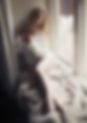 lady in soft white jumper sitting on windowsill looking out of the window - boudoir photographer hampshire