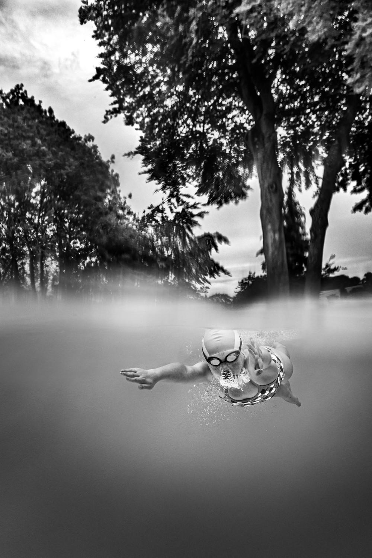 B&W image of girl swimming underwater