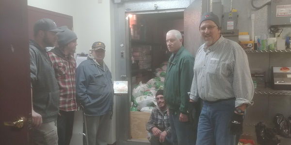 6 members of Lake Delton Lions Club gather around donations of food for local Thanksgiving dinner