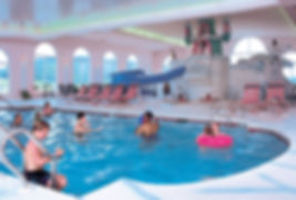 a group of children playiing in an indoor swimming pool and water park at the hotel
