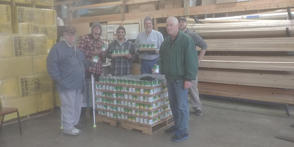 6 members of Lake Delton Lions Club next to pallet of canned vegetables donated for Thanksgiving dinner