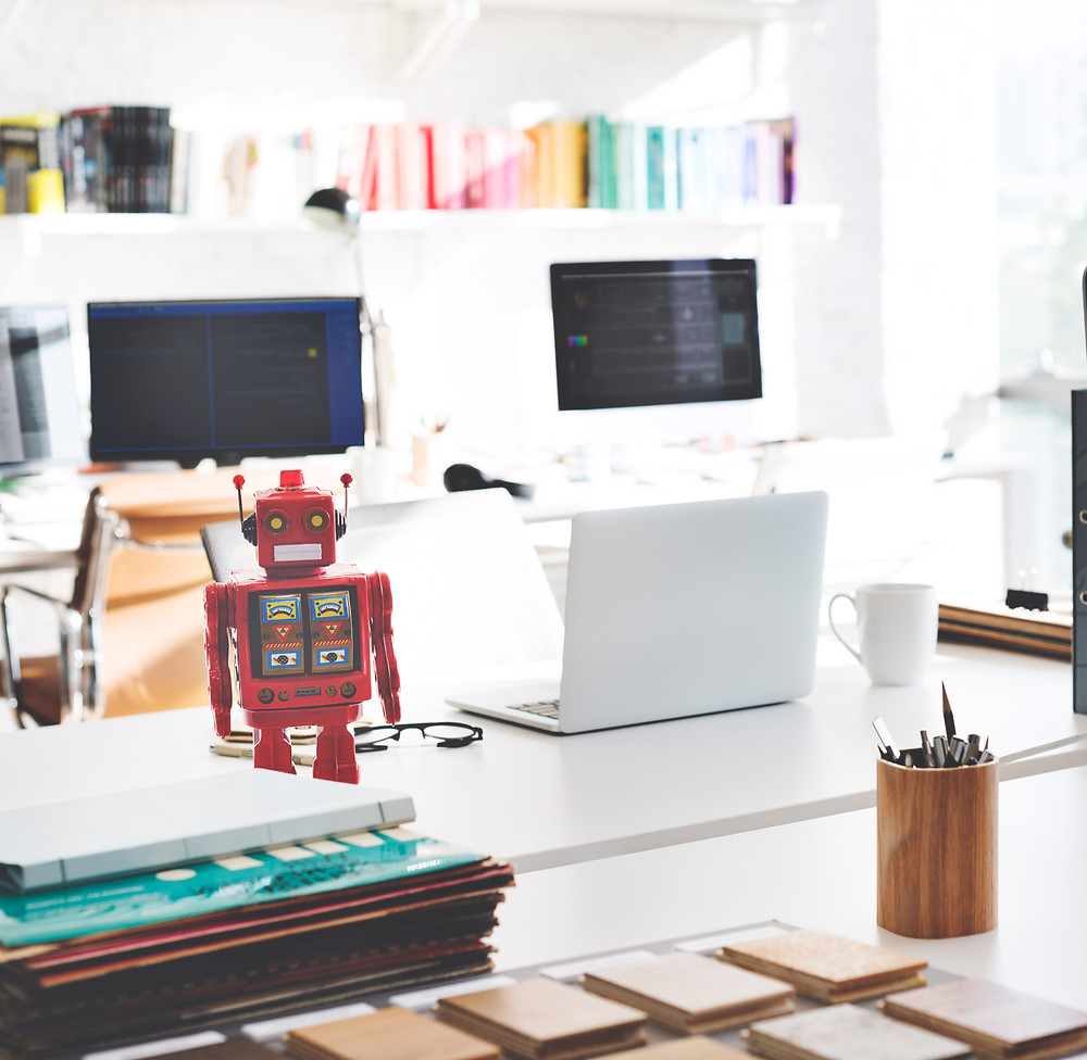 A red toy robot sits on a work table in an office next to an office with other workstations in the background.