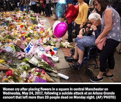 Women cry after placing flowers in a square in central Manchester on Wednesday, May 24, 2017, following a suicide attack at an Ariana Grande concert that left more than 20 people dead on Monday night.