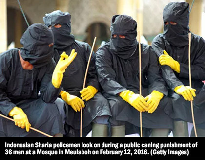Indonesian Sharia policemen look on during a public caning punishment of 36 men at a Mosque in Meulaboh on February 12, 2016.