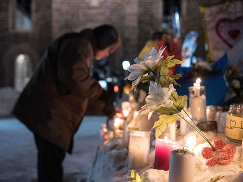 People place candles at a memorial two days after the fatal shooting spree at a Quebec City mosque on Jan. 29, 2017.