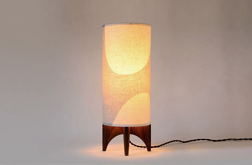 Glowing LUMA table lamp in a home office, front view