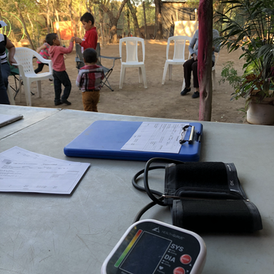 A volunteer takes blood pressures and histories for patients as part of our rural outreach community health clinic