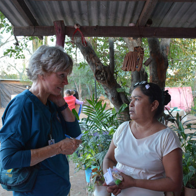 Dr. Janet Lapp speaks with a local woman as she receives care in a rural community health clinic