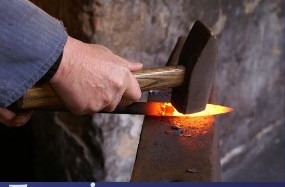 Man with heavy hammer blows red-hot iron on the anvil. He is shaping his character traits with skill and patience.