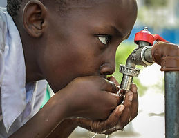African boy drinking water from outdoor faucet