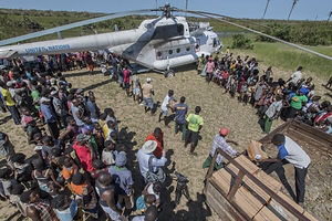 people unloading emergency supplies from United Nations helicopter