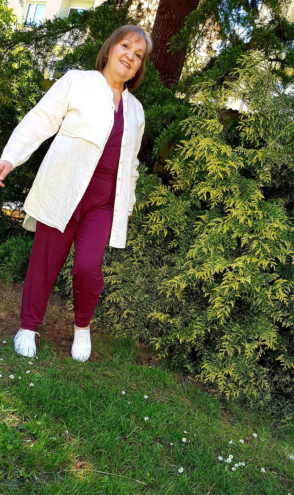 Frau vor gründen Büschen mit beiger Bluse, rotem Jumpsuit und weißen Sneekers.