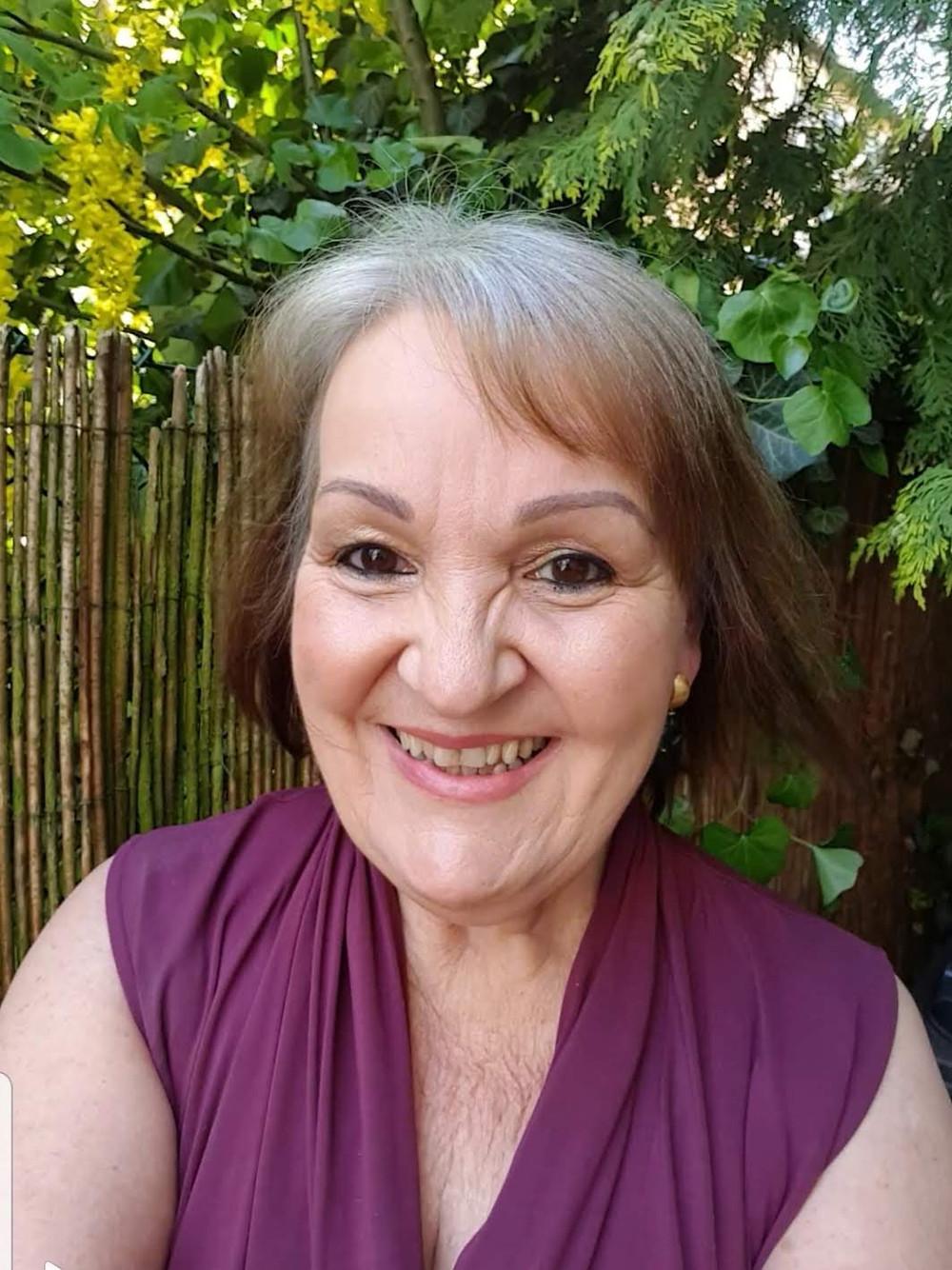 Frauenmit wehenden Haaren im Portrait. Strahlend lachend mit rotem ärmellosen Jumpsuit