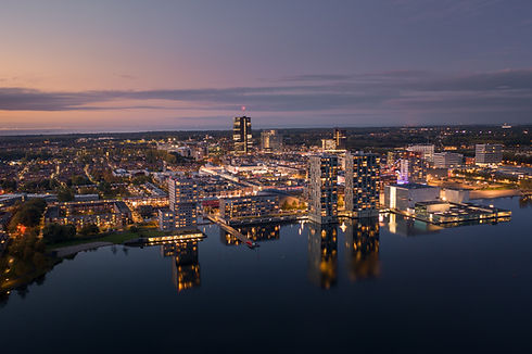 Almere city center with its modern architecture illuminated at dusk, with beautiful reflec...ew..jpg