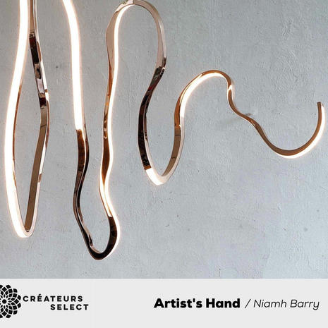 Artist's Hand Niamh Barry  - This series is based on the concept of drawing with bronze in mid air.  As each piece within this series is created, every one of the works will be site and client specific and will therefore be completely unique. Working entirely by hand allows for endless possibilities of varying forms and the finishes can vary from the brightest mirror polished bronze to the deepest of dark patinas.  The illumination of each piece can be controlled to be a subtle line of light or to give a stronger and more definite light emission.