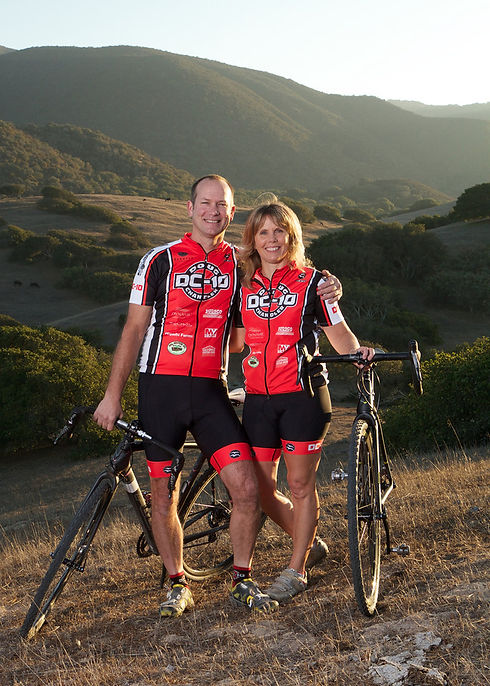 A photo of two people, Doug Chandler and Sherry Chandler, wearing DC-10 cycling jerseys. They're standing outside and there are hills behind them. They are holding two bicycles and smiling.