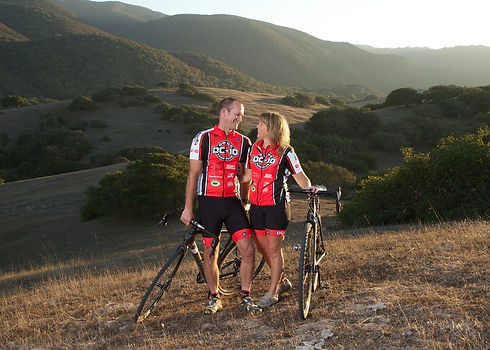 A photo of two people, Doug Chandler and Sherry Chandler, wearing DC-10 cycling jerseys. They're standing outside and there are hills behind them. They are holding two bicycles and smiling, looking at eachother.