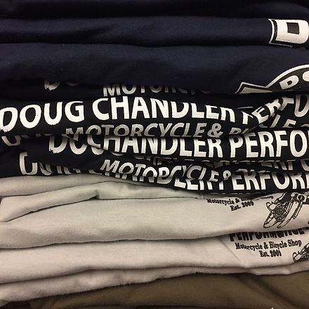 A stack of folded custom dc-10 doug chandler performance t-shirts
