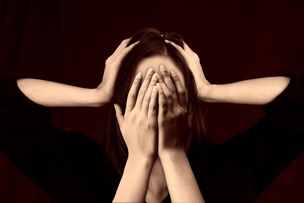 Une femme se cache le visage dans ses mains