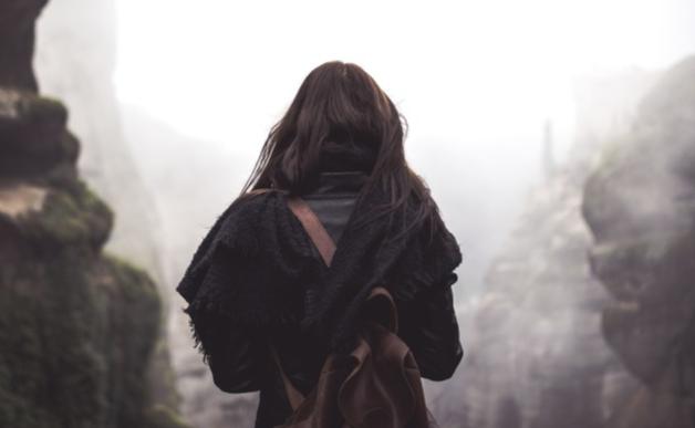 Image en noir et blanc représentant une jeune fille de dos, partant dans le brouillard