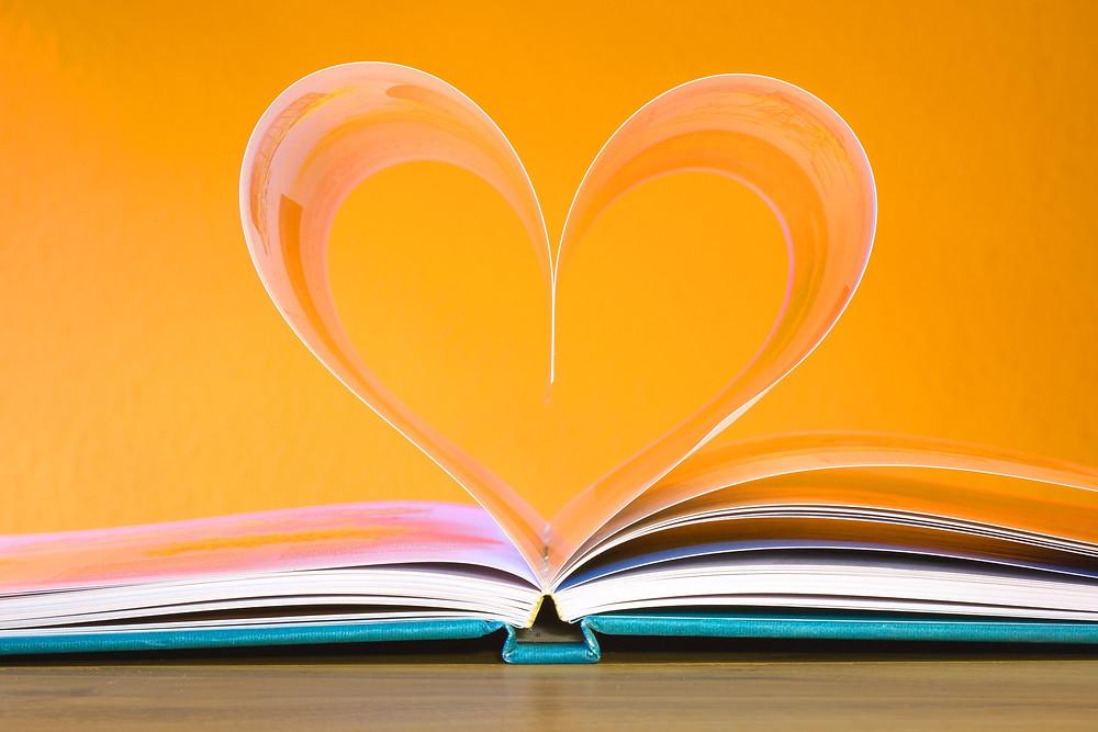 Un livre ouvert sur fond orange et cœur en transparence placé à la pliure