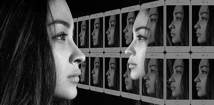 Jeune femme de profil devant un écran multipliant l'image de son visage, à la découverte de soi