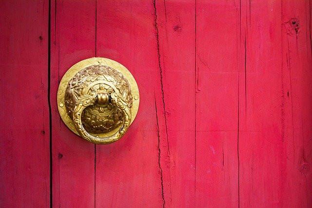 Poignée dorée sur porte en bois de couleur rose framboise