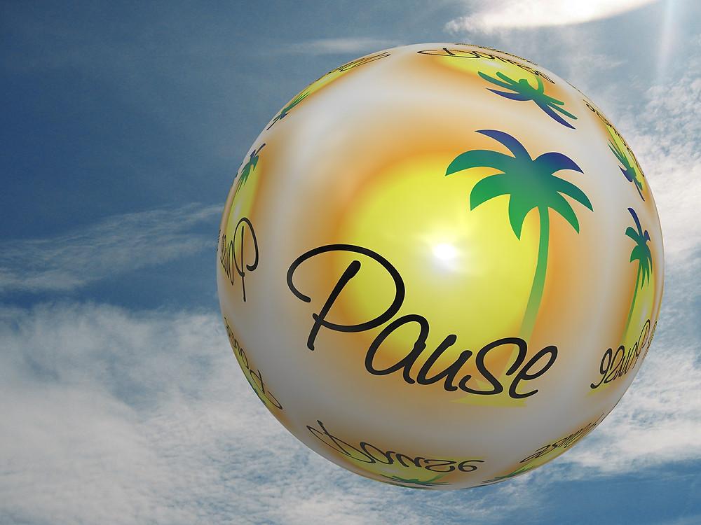 Une boule dans l'espace avec en décor : un palmier, le mot Pause