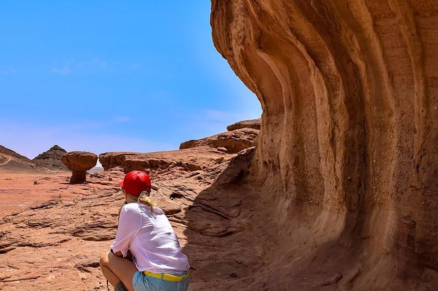 Femme de dos, accroupie devant une étendue de désert en Israël