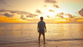 Homme face à l'océan au soleil couchant