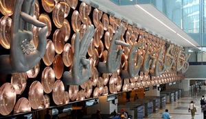 Image représentant un mur de l'aéroport de New Delhi, couvert de mains en position de mudras