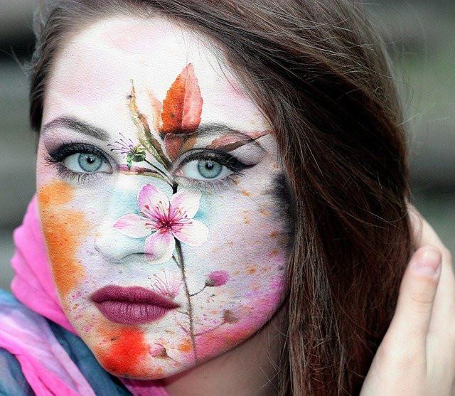 Jeune femme au visage peint d'une fleur traversant tout le côté gauche de son visage, comme les émotions
