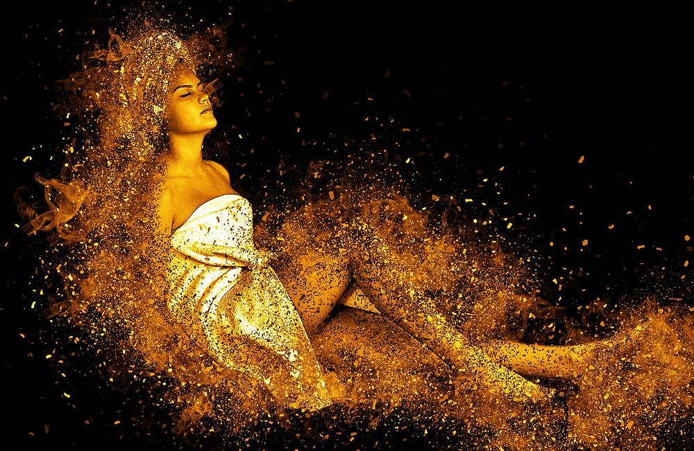 Une femme, les yeux clos, enroulée dans un drap entourée d'un halo de poussière dorée