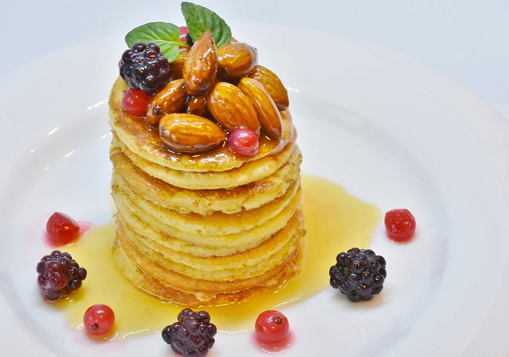 Pile de pancakes décorés d'amandes et de fruits rouges