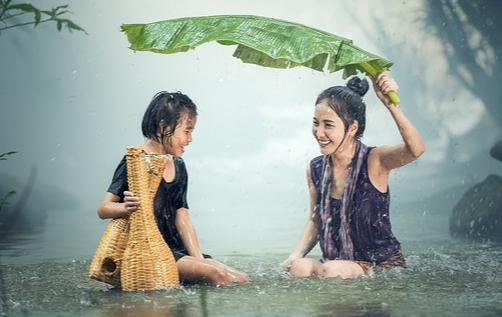 En Thaïlande, mère et fille sont sous la pluie et s'abritent sous une feuille de bananier