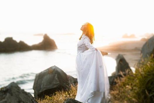 Femme vêtue d'une grande robe blanche, bord de mer dans une grande inspiration