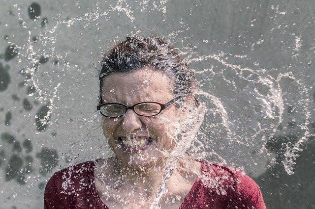 Jeune femme porteuse de lunettes s'ébroue comme pour chasser des émotions négatives