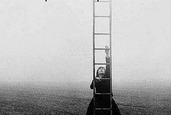 Photo en noir et blanc, un femme montant une échelle se trouve au premier barreauem