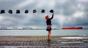 Une jeune femme sur une jetée, un chapeau à la main et six autres suspendus dans l'espace derrière elle