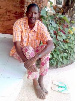 Demba assis devant une case