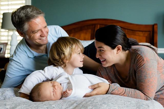 Une famille sur un lit composée de la mère, du père d'un petit garçon et d'un bébé