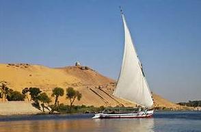 Felouque naviguant sur le Nil et dépassant une oasis