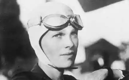 Amelia Earhart casquée, portant lunettes aux commandes de son avion