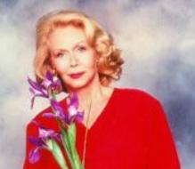 Portrait de Louise Hay en  pull rouge portant des fleurs
