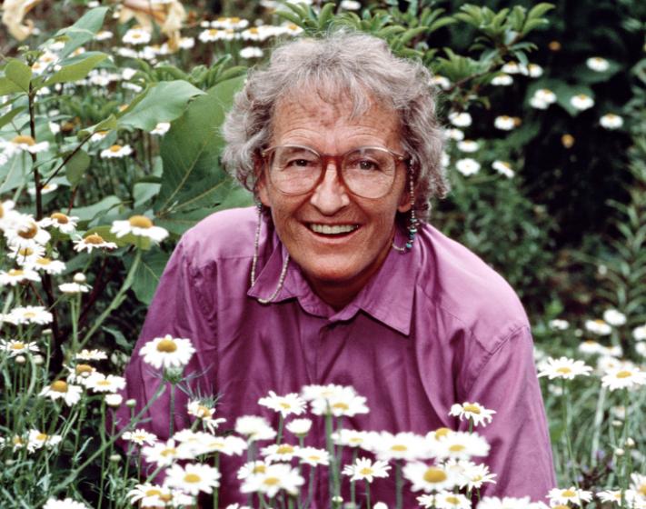 Portrait photo de Elisabeth Kübler-Ross dans un champ de marguerites