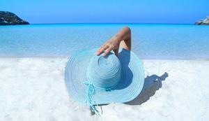 Femme face à la mer, retenant d'une main son chapeau de paille bleue