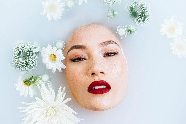 Visage de femme émergeant d'une nappe blanche, entourée de fleurs, cultivant ses émotions comme un jardin intérieur