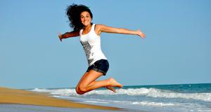 Une jeune femme saute en l'air avec la mer et le ciel en toile de fond