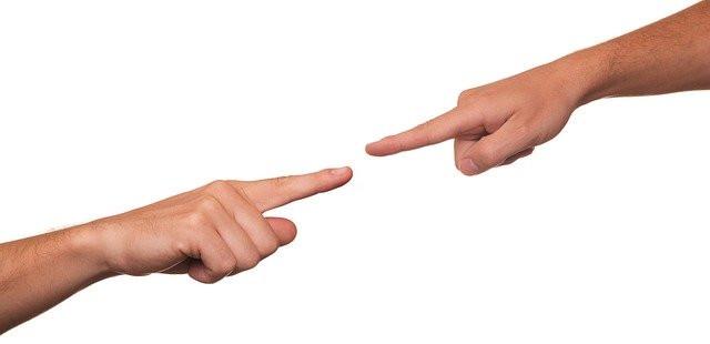 Deux bras tendus, l'un vers l'autre, pointant chacun  leur index