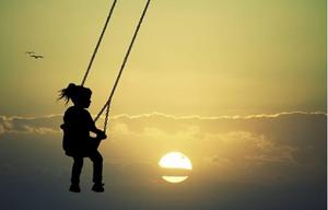 Une enfant fait de la balançoire au milieu du ciel